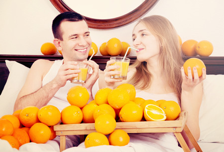 Young cheerful smiling couple with ripe oranges and freshly squeezed juice Stock Photo