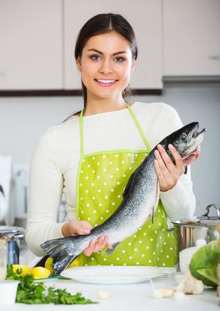 jorobado: niña feliz en el suéter blanco con pescado salmón fresco