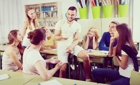 informal clothes: Friendly students talking during a break between lessons in college