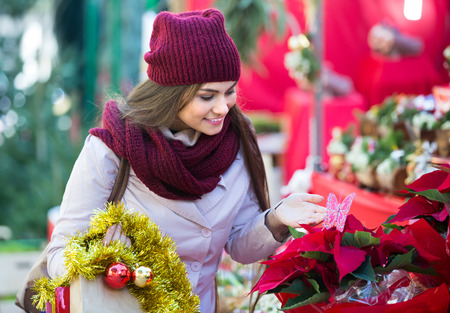 lifestile: Young woman buying floral compositions at Christmas market
