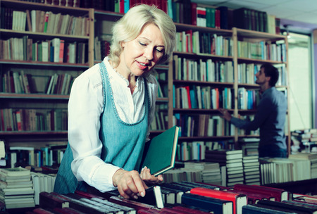 portrait of mature woman 60-65 yrars old standing among bookshelves and looking for book