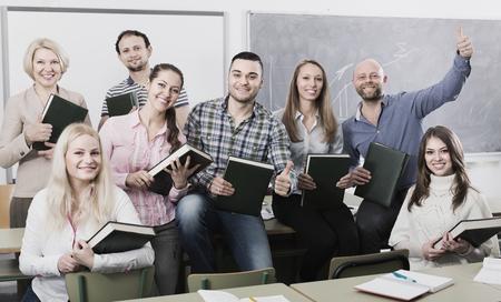 Groupe d'étudiants adultes gais et entraîneur posant à une session de formation scolaire. Mise au point sélective