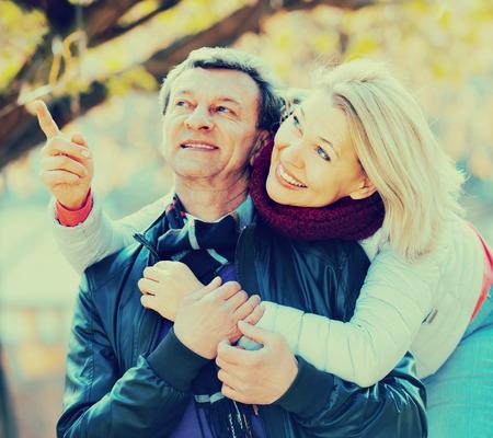 cuddling: Portrait of joyful elderly couple cuddling in park and laughing. Focus on woman