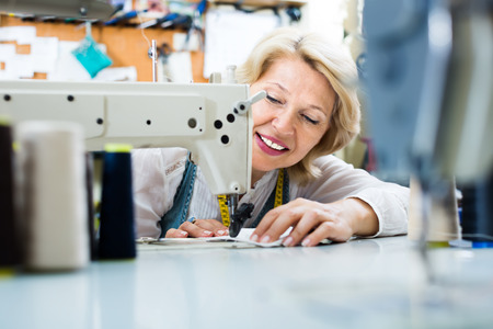 cheerful middle-aged female tailor using sewing machine at workshop Stock Photo