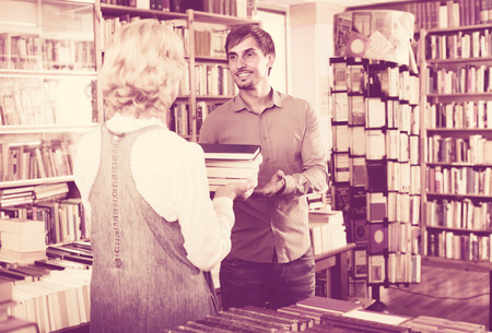 50s: cheerful mature woman 50s and young man having books in hands in book shop
