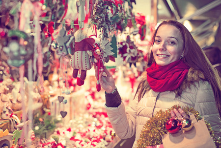 overspending: Joyful longhaired brunette choosing gifts and decorations at Christmas fair in evening