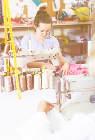 young professional female tailor using sewing machine at workshop Stock Photo