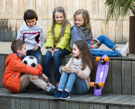 blabbing: Group of children with ball and skateboard chatting outdoors in sunny day