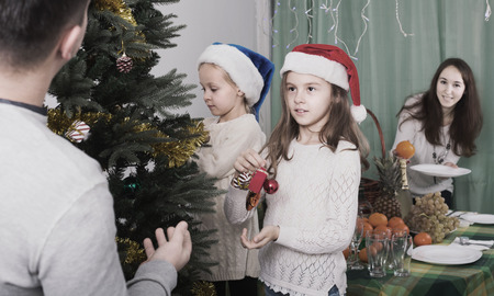 decorating christmas tree: Happy family with children decorating Christmas tree at home Stock Photo