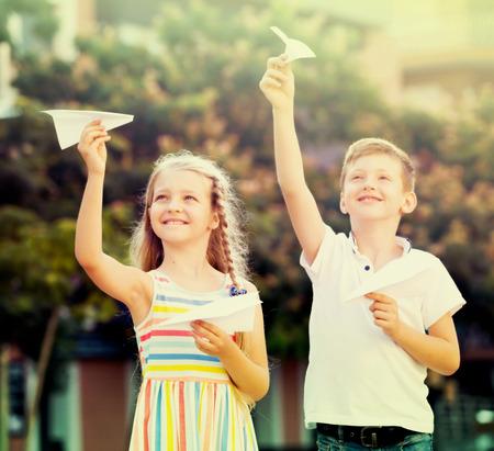 niÑos contentos: dos niños alegres que juegan con los planos de papel en la ciudad el día de verano