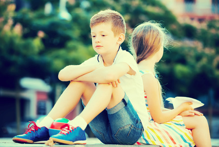 social outcast: Portrait of upset boy sitting back to friend outdoors in park
