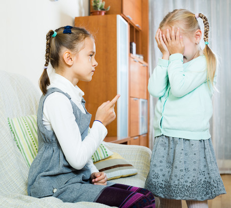 shaming: Annoying big sister preaching little one and shaking finger in apartment