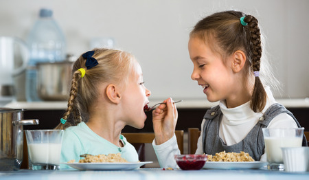 Portrait of  two cheerful little girls eating porridge with jam in kitchen