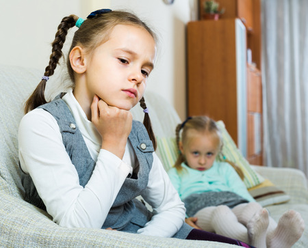 Offended little sisters sitting apart of each other after argue at home Stock Photo
