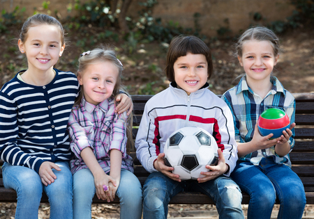 normal school: Smiling little kids posing together with ball outdoor in city street