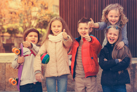 normal school: Group of cheerful children posing at urban street in sunny day Stock Photo