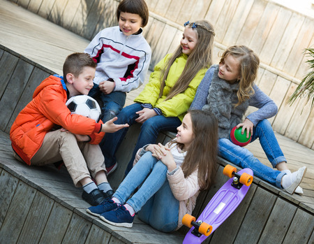blabbing: Group of children 9s with ball and skateboard chatting outdoors Stock Photo