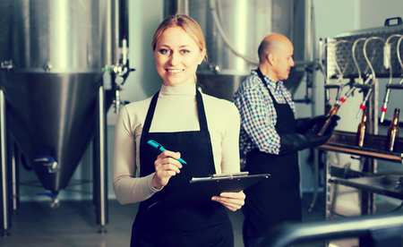 brewery: Portrait of joyful young female technologist on beer brewery factory