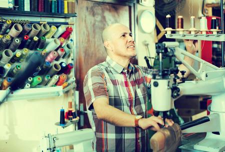 broaching: Smiling shoemaker stitching footwear on machine in shoe atelier