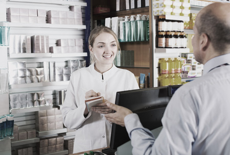 personas enfermas: Friendly smiling young female pharmacist serving mature man in pharmacy