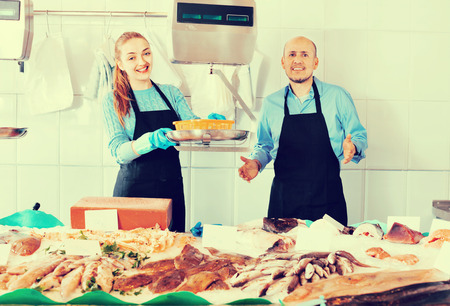 Ordinary fish and seafood store with two pleasant smiling friendly sellers indoors Stock Photo