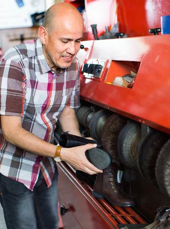 atelier: Professional craftsman polishing footwear on machine in shoe atelier