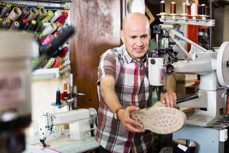 clicker: Mature shoemaker stitching footwear on machine in shoe atelier