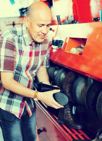 footwear: Professional craftsman polishing footwear on machine in shoe atelier