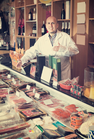 wurst: Male seller with wurst and jamon in meat store