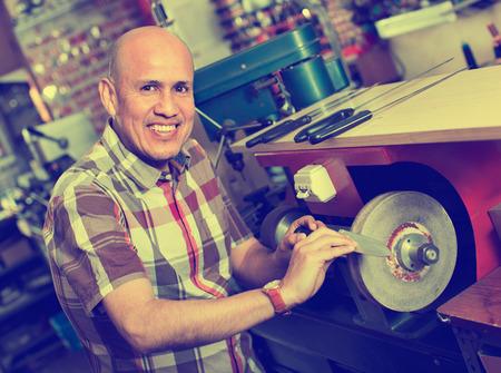 Portrait of efficient positive specialist sharpening steel knife on  wheel lathe