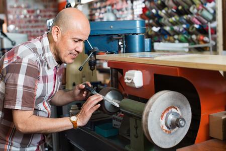 diligente: Portrait of diligent elderly specialist sharpening steel knife on  wheel lathe