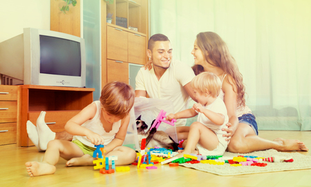 Smiling young parents and two daughters relaxing with toys in home