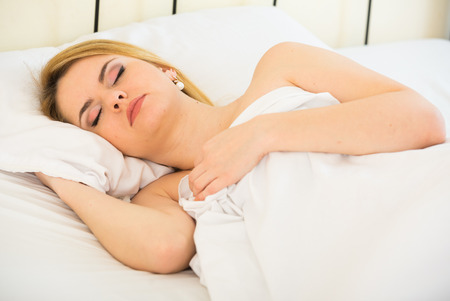 drowse: Blond girl having a nap in bed at home Stock Photo