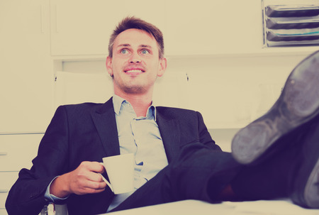feet on desk: Young relaxed man in formalwear sitting with feet up on desk at company office
