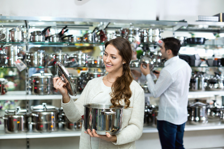 cookware: Cheerful cute couple in the cookware section at hypermarket Stock Photo