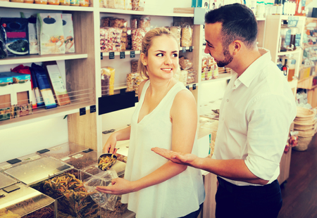 joyful smiling young couple selecting various groats in the store with ecological goods