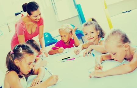 diligente: Ni�os sonrientes diligentes escrito, junto con el tutor de la clase de la escuela en el interior Foto de archivo