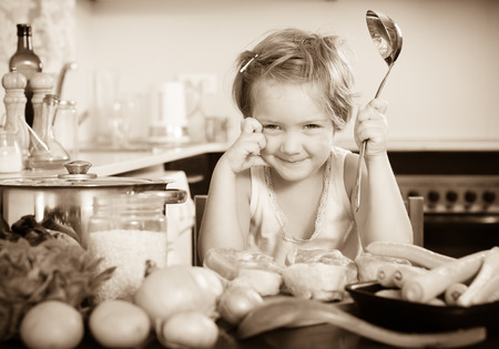 Happy smiling baby girl cooking with meat at home Stock Photo