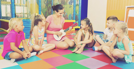 ni�os contentos: Smiling glad children sitting with teacher holding ukulele and listening to music in class at school