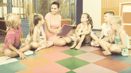 careful: Group of careful children sitting with teacher and listening to book in class at school