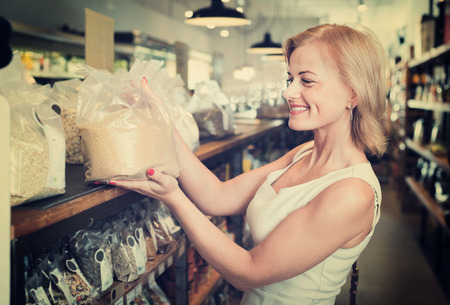 gladly: Portrait of happy charming young woman gladly shopping groats in supermarket
