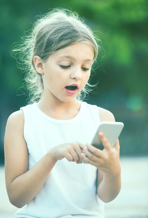 gasping: Portrait of surprised girl looking at mobile phone outdoors