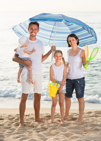 russian man: Happy russian man and woman with two kids standing together under beach umbrella on beach Stock Photo