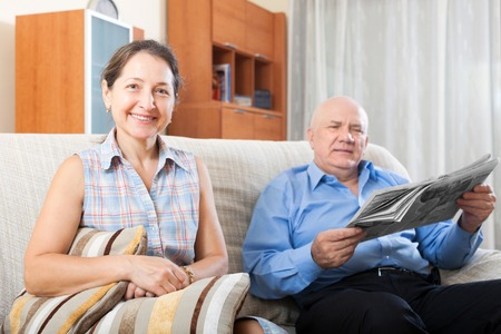 gladful: Portrait of smiling happy grandparents on the couch at home with newspaper Stock Photo
