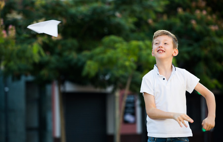 glad: portrait of glad boy throwing  paper airplanes in park on summer day