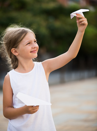 simple girl: happy girl playing with simple paper airplane toy on sunny day in town Stock Photo