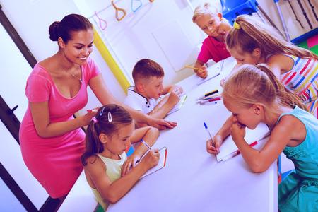 diligente: niños diligentes aprender a escribir en la lección de clase de la escuela primaria