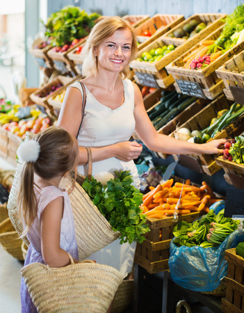 Glad  young mother with  happy smiling daughter shopping various veggies in food store