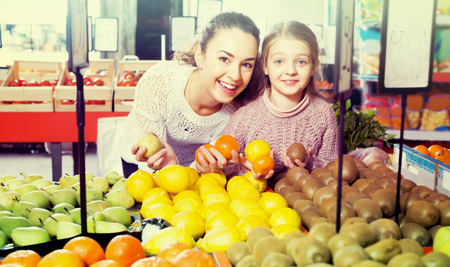purchasers: Cheerful smiling young woman with little daughter purchasing fruits at market