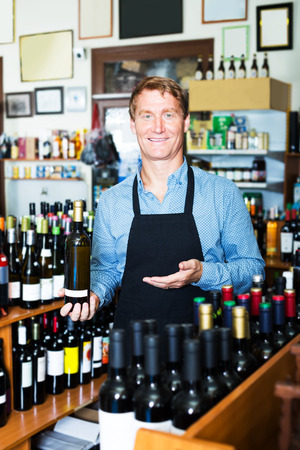 promoting: Glad seller man in apron promoting bottle of wine in wine house Stock Photo